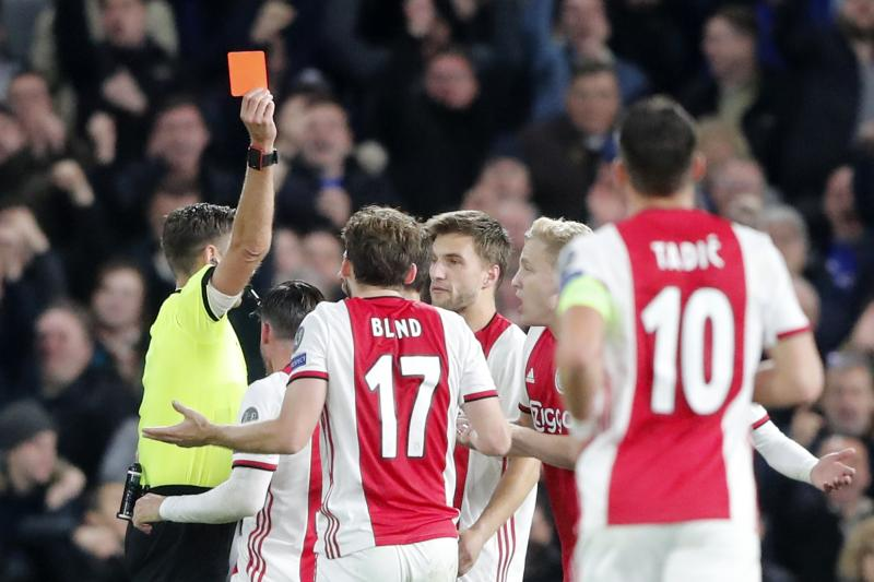 Referee Gianluca Rocchi shows a red card to Ajax's Daley Blind during the group H Champions League soccer match between Chelsea and Ajax at Stamford Bridge in London, Tuesday, Nov. 5, 2019. (AP Photo/Frank Augstein)