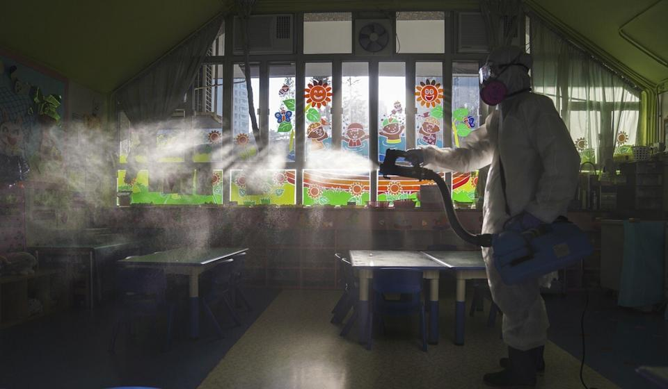 Workers spray disinfectant at Tai Po Methodist kindergarten after a seasonal influenza outbreak. Photo: Sam Tsang