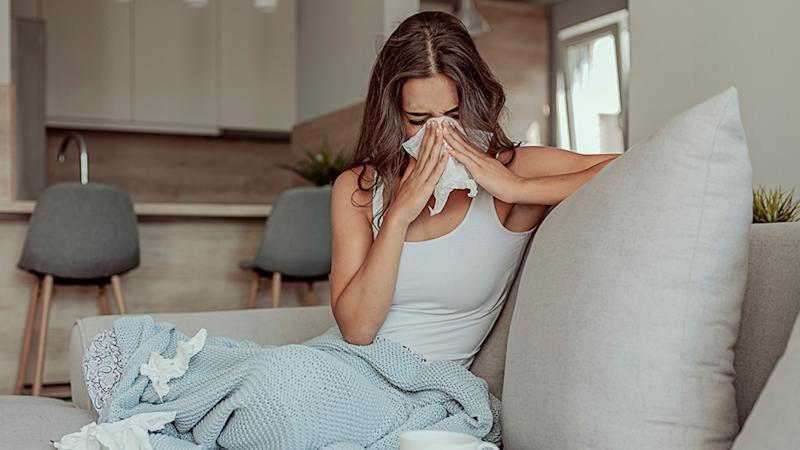 Woman with a cold sneezes