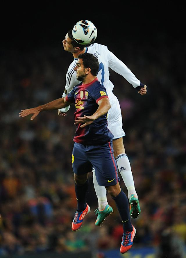 BARCELONA, SPAIN - OCTOBER 07: Cristiano Ronaldo (Top) of Real Madrid duels in the air for the ball with Martin Montoya of Barcelona during the la Liga match between FC Barcelona and Real Madrid at the Camp Nou stadium on October 7, 2012 in Barcelona, Spain. (Photo by Jasper Juinen/Getty Images)