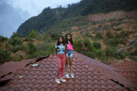 Twins Dulce Alejandra Mejia, right, and Genesis Mejia, 12, stand for a portrait on the roof of their neighbor's home devastated by hurricanes Eta and Iota in the village of La Reina, Honduras, Saturday, June 26, 2021. Their parents live in Spain. Home to about 1,000 people, the town in western Honduras that was hit by two powerful hurricanes within three weeks, natural disasters made far worse by local deforestation and climate change. (AP Photo/Rodrigo Abd)