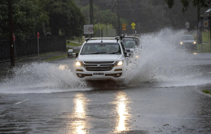 Vehicles plow through water on a flooded road at Port Stephens, 200 kilometers (120 miles) north of Sydney, Australia, Sunday, March 21, 2021. Residents across the state of New South Wales have been warned to prepare for possible evacuations, as NSW Premier Gladys Berejiklian said the state's flood crisis would continue for several more days. (AP Photo/Mark Baker)
