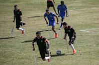 Palestinian footballers compete in the final of a local championship for amputees between Al-Jazeera (black kit) and Al-Abtal (blue kit) organised by the International Committee of the Red Cross and the Palestinian Football Association in Gaza City