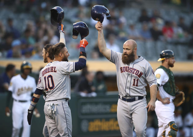 Houston Astros' Evan Gattis, right, celebrates with Yuli Gurriel (10) and Josh Reddick, left, after hitting a three-run home run off Oakland Athletics' Emilio Pagan during the second inning of a baseball game Wednesday, June 13, 2018, in Oakland, Calif. (AP Photo/Ben Margot)