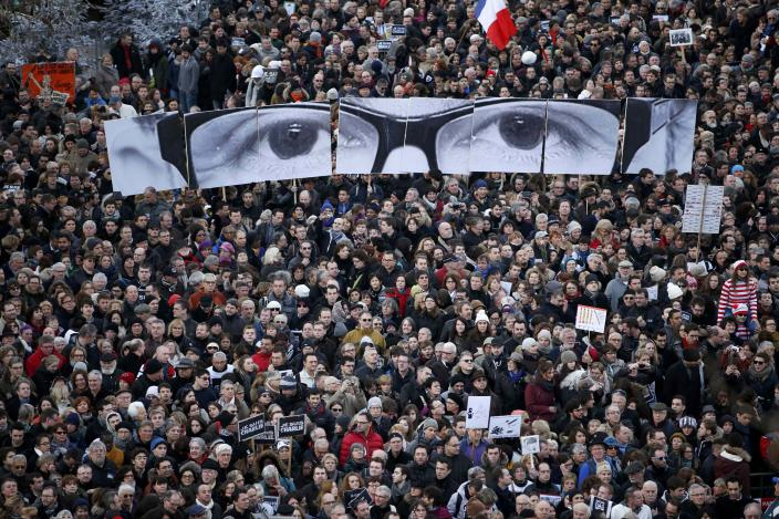 """REFILE - ADDITIONAL CAPTION INFORMATION People hold panels to create the eyes of late Charlie Hebdo editor Stephane Charbonnier, known as """"Charb"""", as hundreds of thousands of French citizens take part in a solidarity march (Marche Republicaine) in the streets of Paris January 11, 2015. French citizens, joined by dozens of foreign leaders, among them Arab and Muslim representatives, took part in a march on Sunday in an unprecedented tribute to this week's victims following the shootings by gunmen at the offices of the satirical weekly newspaper Charlie Hebdo, the killing of a policewoman in Montrouge, and the hostage-taking at a kosher supermarket at the Porte de Vincennes. REUTERS/Yves Herman (FRANCE - Tags: CRIME LAW POLITICS CIVIL UNREST TPX IMAGES OF THE DAY SOCIETY)"""