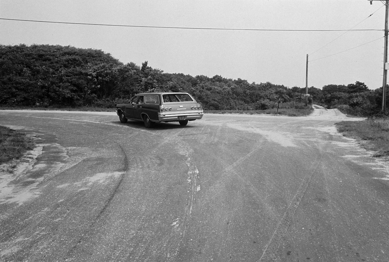 <p>A car follows the curve of Chappaquiddick Road to the left on Chappaquiddick Island near Edgartown, Mass., on Aug. 9, 1969. Cemetery Road is straight ahead. On the night of his car accident with Mary Jo Kopechne, Ted Kennedy turned right onto Dike Road and drove off the bridge farther down. (Photo: Bettmann/Getty Images) </p>