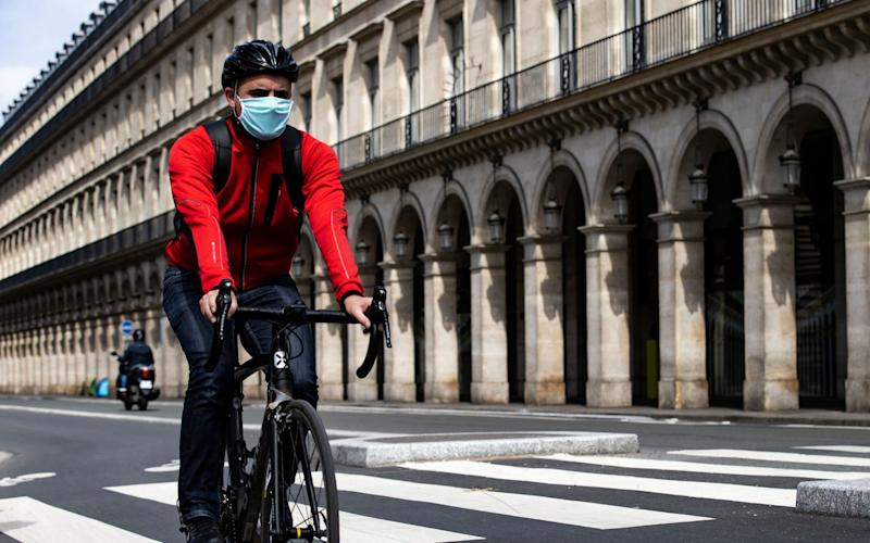 A man cycles down Rue de Rivoli in Paris, France - IAN LANGSDON/EPA-EFE/Shutterstock