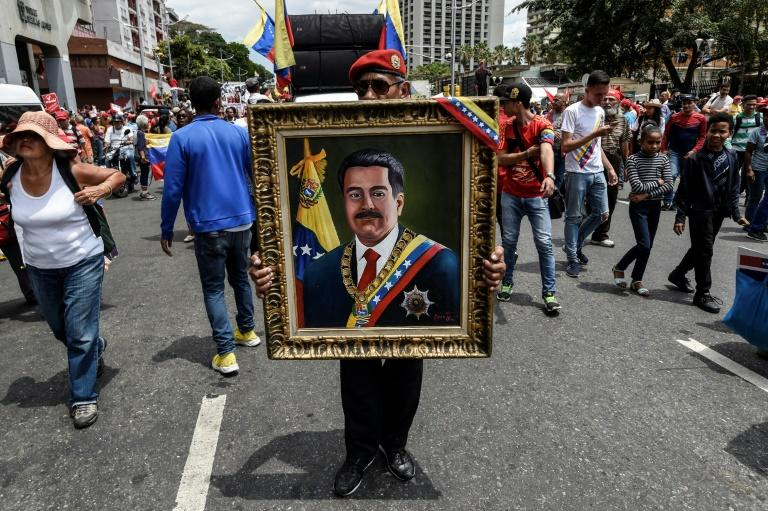 A painting depicting Venezuelan President Nicolas Maduro is displayed by a supporter during a pro-government demonstration in Caracas