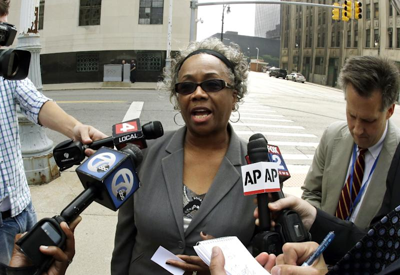 """Detroit resident Olivia Gillon addresses the media outside federal court in Detroit, Thursday, Sept. 19, 2013 after attending a Detroit bankruptcy hearing. Dozens of residents have told a judge why they oppose Detroit's bankruptcy, but they had to do it in three minutes or less. """"I was actually not looking for my day in court. Some people did thank the judge for giving them their day in court. I simply received a notice in the mail, read it, tried to understand it, realized that they were treating me as an individual creditor and felt like I needed to respond."""" (AP Photo/Carlos Osorio)"""