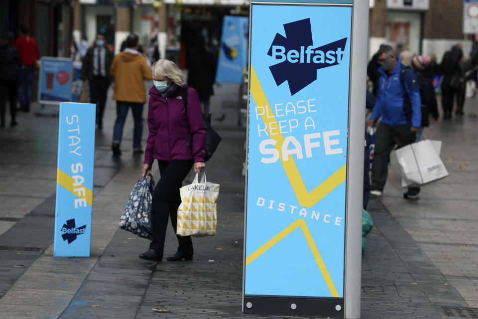 """A woman wears a face mask in Belfast city centre, Northern Ireland, Wednesday, Oct. 14, 2020. Northern Ireland introducing the tightest COVID-19 restrictions in the United Kingdom on Wednesday, closing schools for two weeks and pubs and restaurants for a month. """"This is not the time for trite political points,"""" First Minister Arlene Foster told lawmakers at the regional assembly in Belfast. """"This is the time for solutions."""" (Brian Lawless/PA via AP)"""