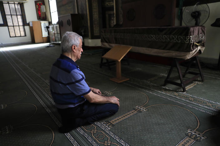 The father of Ibrahim Harb, 35, a Lebanese man who was critically injured in the massive explosion at Beirut's port last year and who died on Monday nearly 14 months after the blast, prays at a mosque next of his son's coffin in Beirut, Lebanon, Tuesday, Sept. 28, 2021. On August 4, 2020, hundreds of tons of ammonium nitrate, a highly explosive material used in fertilizers, ignited after a massive fire at the port. The death brings to at least 215 the number of people who have been killed by the blast, according to official records. (AP Photo/Hussein Malla)