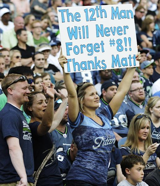 Fans of Tennessee Titans quarterback Matt Hasselbeck cheer in the first half of an NFL football preseason game against his former team, the Seattle Seahawks, Saturday, Aug. 11, 2012, in Seattle. (AP Photo/Rick Bowmer)