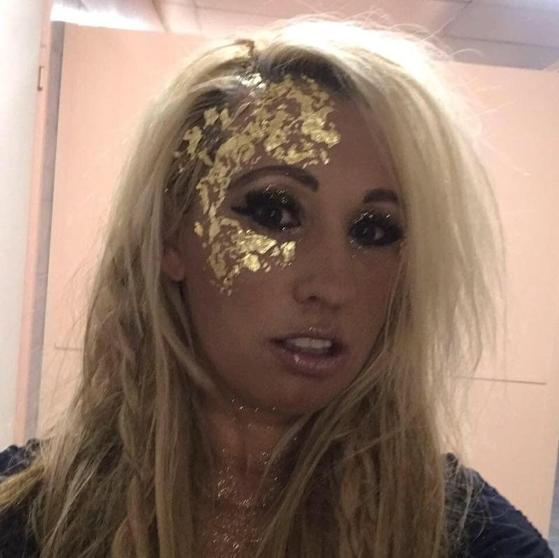 A photo of Domanique O'Reilly ready for an event with gold glitter painted on her face.