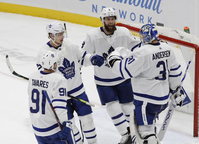 Toronto Maple Leafs goaltender Frederik Andersen (31) celebrates with teammates Jake Muzzin (8), Nikita Zaitsev (22) and John Tavares (91) after an NHL hockey game against the New York Islanders Monday, April 1, 2019, in Uniondale, N.Y. The Maple Leafs won 2-1. (AP Photo/Frank Franklin II)