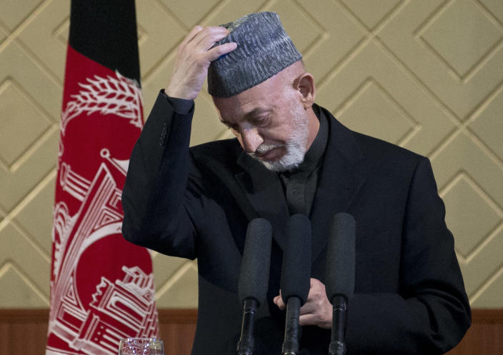 "Afghan President Hamid Karzai takes off his hat during a ceremony at Kabul University in Kabul, Afghanistan, Thursday, May 9, 2013. Karzai said he is ready to let the U.S. have nine bases in the country after the 2014 combat troop pullout, but wants Washington's ""security and economic guarantees"" first. (AP Photo/Anja Niedringhaus)"