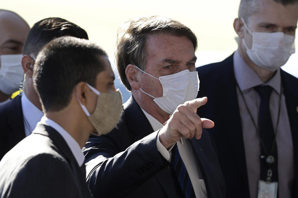 Brazil's President Jair Bolsonaro wears a face mask as he speaks to the press upon departure from the official residence of Alvorada palace in Brasilia, Brazil, Monday, May 11, 2020. Starting Monday, the capital city's government will fine or jail those who do not wear a face mask in public, amid the spread of the new coronavirus. (AP Photo/Eraldo Peres)
