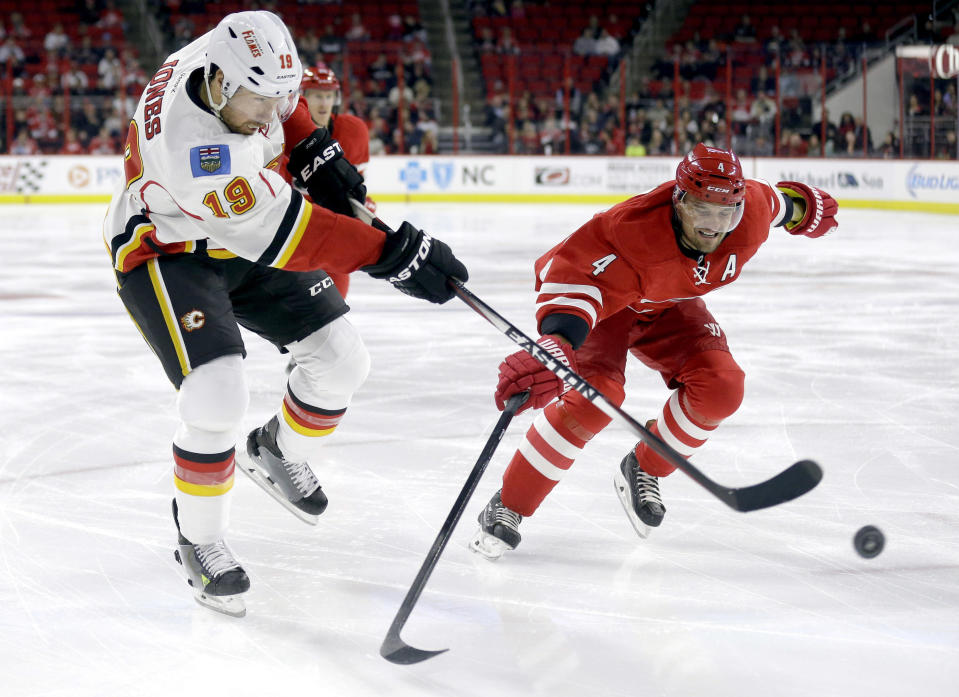 Calgary Flames' David Jones (19) shoots the puck as Carolina Hurricanes' Andrej Sekera (4), of Slovakia, defends during the first period of an NHL hockey game in Raleigh, N.C., Monday, Nov. 10, 2014. (AP Photo/Gerry Broome)