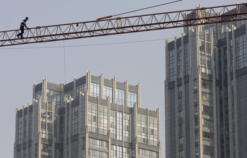 A labourer walks on a crane at a construction site in Nanjing