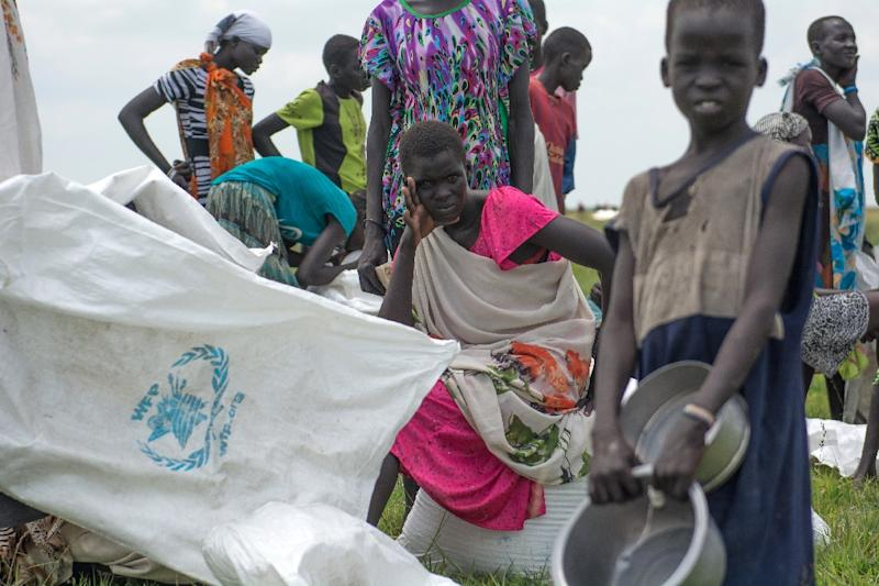 Internally displaced women and children wait for their food ration after an humanitarian airdrop by World Food Programme in a small locality in Mayendit County of Unity State on July 25, 2015 (AFP Photo/Charles Lomodong)