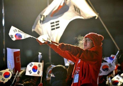 <p>A supporter of South Korea's presidential candidate Park Geun-Hye of the ruling New Frontier Party waves national flags during an election rally in Seoul on December 18, 2012.</p>