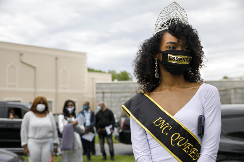 """Sasha Kayla, a Queen with Models Inc., wears a sash, tiara, and face mask that says """"essential"""" as she attends the memorial service for Joanne Paylor, 62, of southwest Washington, at Cedar Hill Cemetery in Suitland-Silver Hill, Md., Sunday, May 3, 2020. Models Inc. is a community organization founded Paylor's son, Iran """"Bang"""" Paylor, that was supported by his mother. Despite not having died from coronavirus, almost every aspect of Paylor's funeral has been impacted by the pandemic. (AP Photo/Jacquelyn Martin)"""