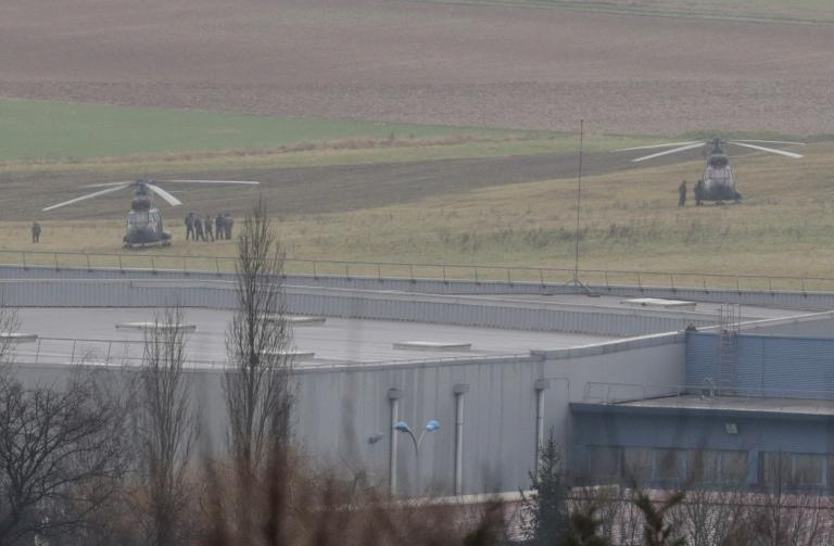 French security forces stand next to helicopters in front of a building in Dammartin-en-Goele