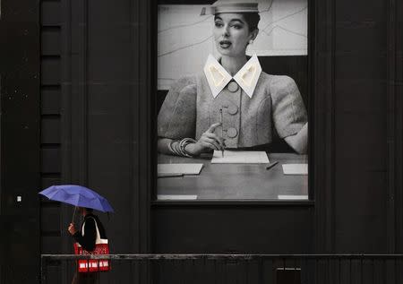 """A man shelters under an umbrella as he passes a display at the Old Street roundabout dubbed """"Silicon Roundabout"""" in London in this May 28, 2013 file photo. REUTERS/Luke Macgregor/Files"""