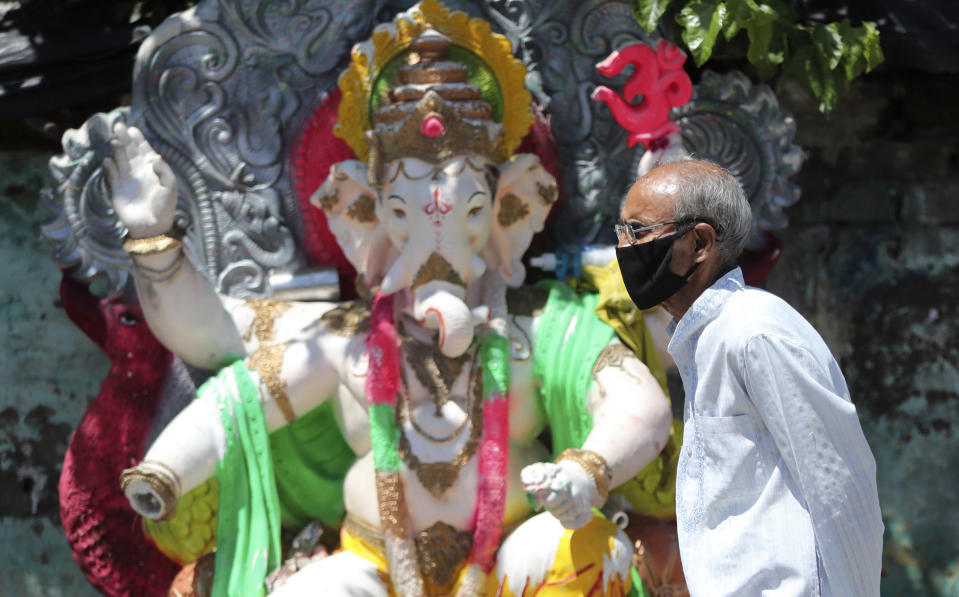 A man wearing a face masks walks past an idol of elephant-headed Hindu god Ganesha during reimposed weekend lockdown to prevent the spread of the coronavirus in Jammu, India Saturday, Aug. 22, 2020. India has the third-highest caseload after the United States and Brazil, and the fourth-highest death toll in the world. (AP Photo/Channi Anand)