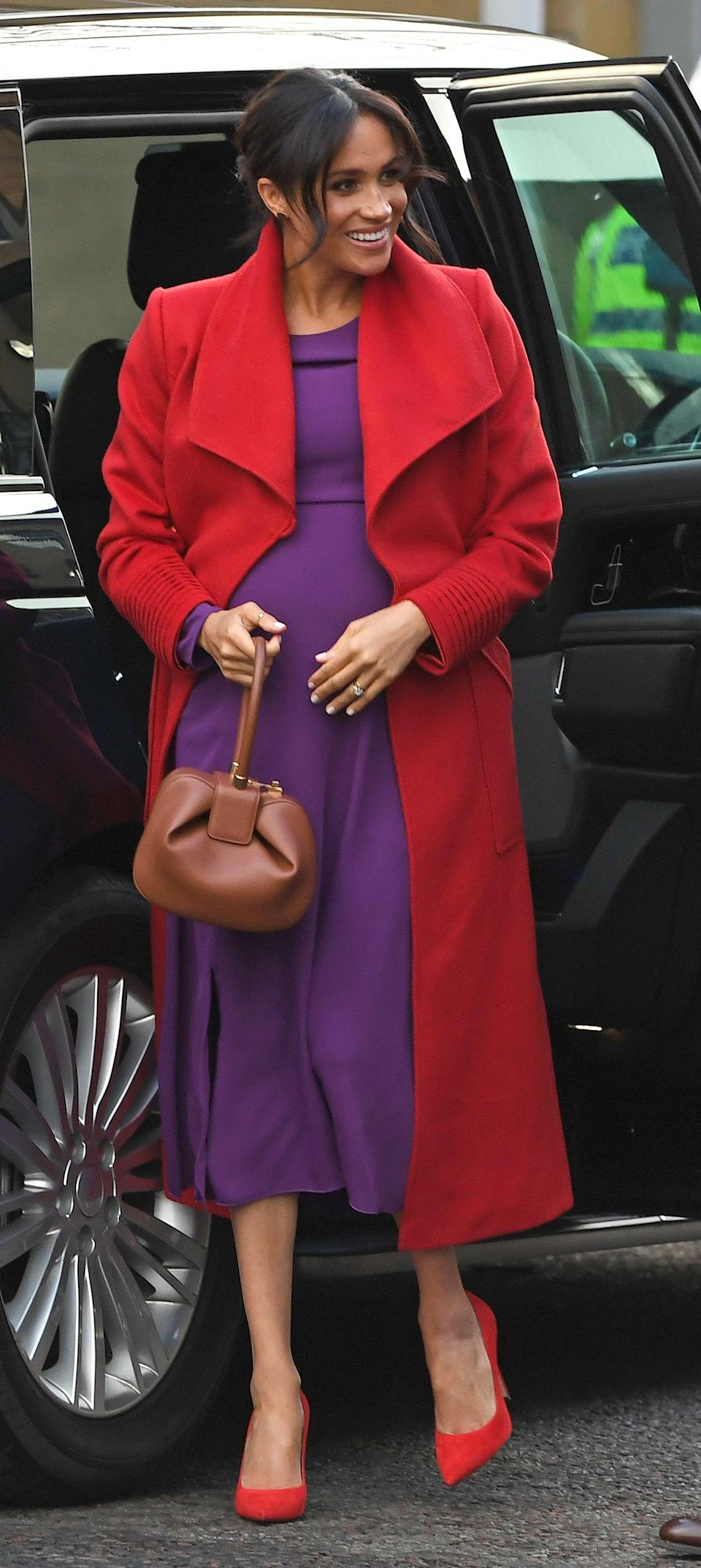 For Harry and Meghan's first joint engagement of 2019, the Duchess of Sussex broke her navy streak in a colour-blocking ensemble by her favourite Canadian brands. The royal dressed her bump in a traffic light red Sentaler coat teamed with a purple midi dress by Aritzia's Babaton. Clashing Stuart Weitzman heels finished the outfit. [Photo: Getty]