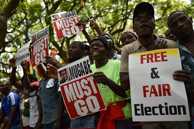 Protesters hold signs during a gathering in Zimbabwe's capital of Harare on Nov. 21, 2017, calling for Mugabe to step down. (TONY KARUMBA via Getty Images)