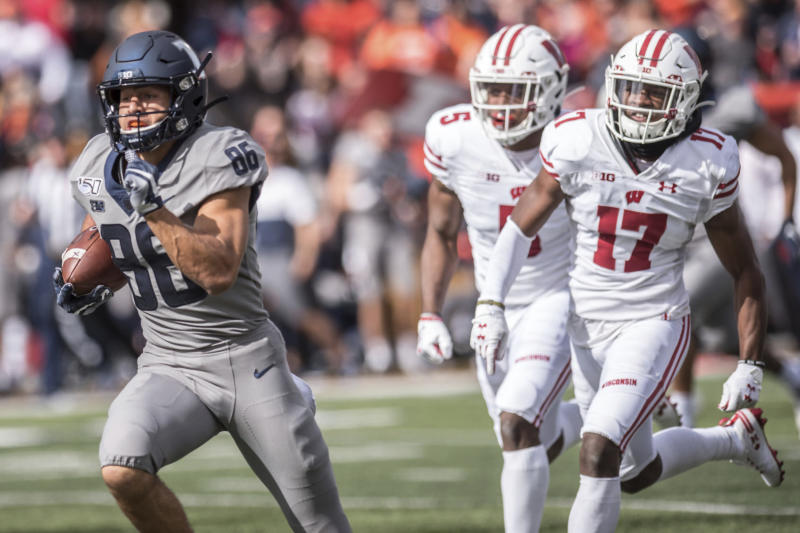 Illinois' Donny Navarro (86) takes the ball in for a touchdown ahead of Wisconsin defenders Rachad Wildgoose (5) and Donte Burton (17) during the first half of an NCAA college football game, Saturday, Oct.19, 2019, in Champaign, Ill. (AP Photo/Holly Hart)