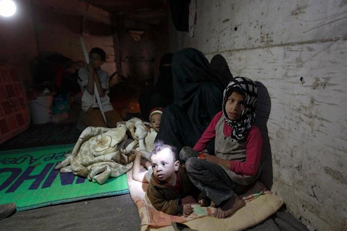 Members of a displaced Yemeni family take shelter in a manmade underground water tunnel after their houses were destroyed by air strikes carried out by the Saudi-led alliance, in Sanaa, on April 30, 2015 (AFP Photo/Mohammed Huwais)