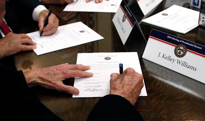 Members of the Mississippi Electoral College sign certificates of vote in the process of formally casting their electoral votes in the 2016 General Election for President and Vice President of the United States at the Capitol in Jackson, Miss., Monday, Dec. 19, 2016. (
