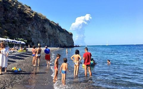 Tourists watch the eruption of the volcano from a neighbouring island - Credit: Twitter