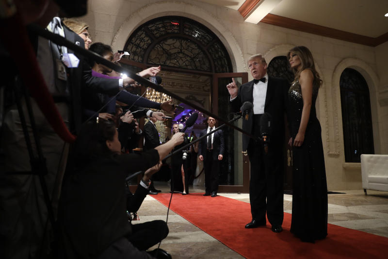 President Donald Trump speaks to the media about the situation at the U.S. embassy in Baghdad, from his Mar-a-Lago property, Tuesday, Dec. 31, 2019, in Palm Beach, Fla., as Melania Trump stands next to him. (AP Photo/ Evan Vucci)
