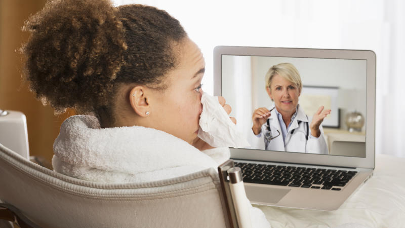 Sick woman video chatting with doctor on laptop