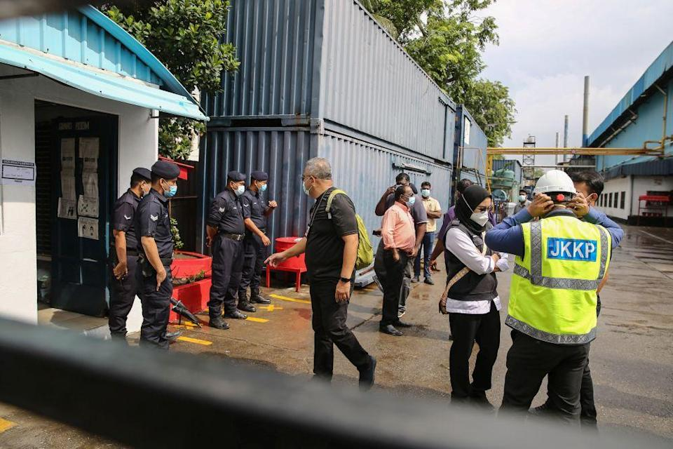 Enforcement officers are pictured during a raid on the premises of a glove manufacturer in Klang December 24, 2020. — Picture by Yusot Mat Isa