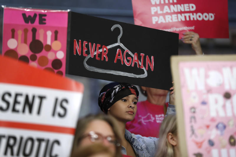 FILE - In this May 21, 2019 file photo, August Mulvihill, of Norwalk, Iowa, center, holds a sign during a rally to protest recent abortion bans at the Statehouse in Des Moines, Iowa. A new report released Wednesday, Sept. 18, shows that the number and rate of abortions across the U.S. have plunged to their lowest levels since the procedure became legal nationwide in 1973. (AP Photo/Charlie Neibergall, File)