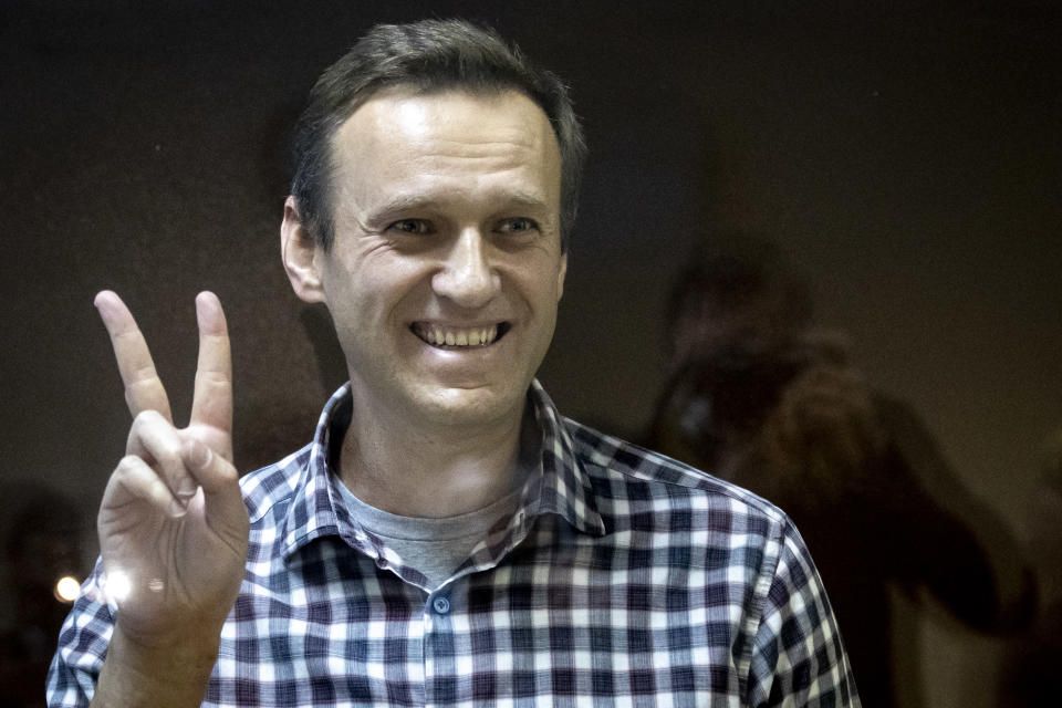 Russian opposition leader Alexei Navalny gestures as he stands behind a grass of the cage in the Babuskinsky District Court in Moscow, Russia, Saturday, Feb. 20, 2021. A Moscow court has rejected Russian opposition leader Alexei Navalny's appeal against his prison sentence. Earlier this month, a lower court sentenced Navalny to two years and eight months in prison for violating terms of his probation while recuperating in Germany from a nerve agent poisoning that he blames on the Kremlin. (AP Photo/Alexander Zemlianichenko)