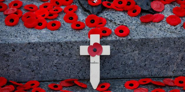 A wooden cross is surrounded by poppies on the Tomb of the Unknown Soldier following Remembrance Day ceremonies at the National War Memorial in Ottawa on Nov. 11, 2017.
