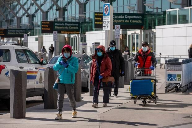 As of Tuesday, international travellers — such as those in this photo taken in March 2020 — will be allowed into Canada without quarantining, provided they are fully immunized with a vaccine approved by Health Canada.  (Ben Nelms/CBC - image credit)