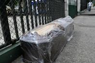 A coffin is seen on the pavement outside the Teodoro Maldonado Hospital in Guayaquil, Ecuador