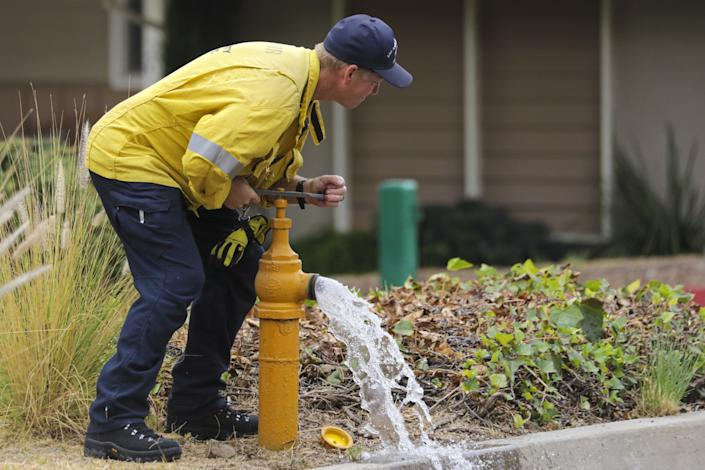 "Los Angeles County firefighter Scott Seymour shuts off a fire hydrant in Duarte. <span class=""copyright"">(Irfan Khan / Los Angeles Times)</span>"