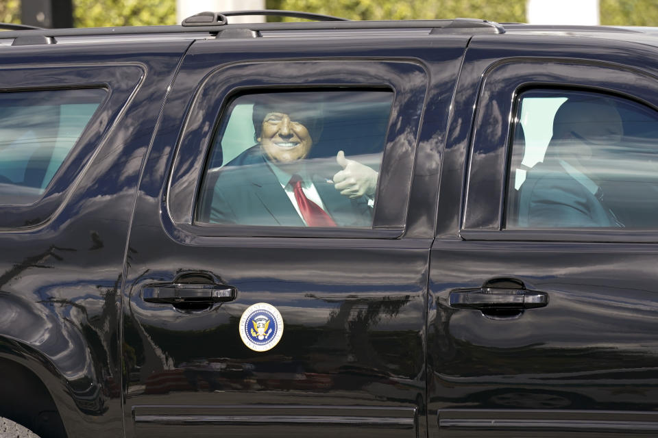 President Donald Trump gestures to supporters en route to his Mar-a-Lago Florida Resort on Wednesday, Jan. 20, 2021, in West Palm Beach, Fla. (AP Photo/Lynne Sladky)