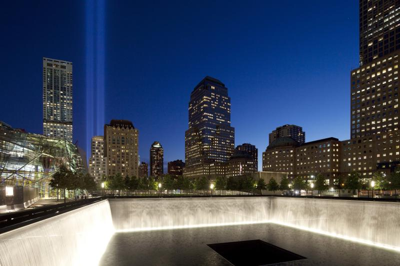 The Tribute in Light, left, shines above a reflecting pool at the National September 11 Memorial, Tuesday, Sept. 11, 2012 in New York. Today marks the 11th anniversary of the terrorist attacks of Sept. 11, 2001. (AP Photo/Mark Lennihan)
