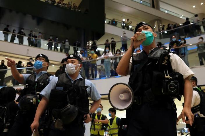 Police wearing face masks to avoid the spread of the coronavirus disease (COVID-19) as they disperse anti-government protesters from a shopping mall after a rally in Hong Kong