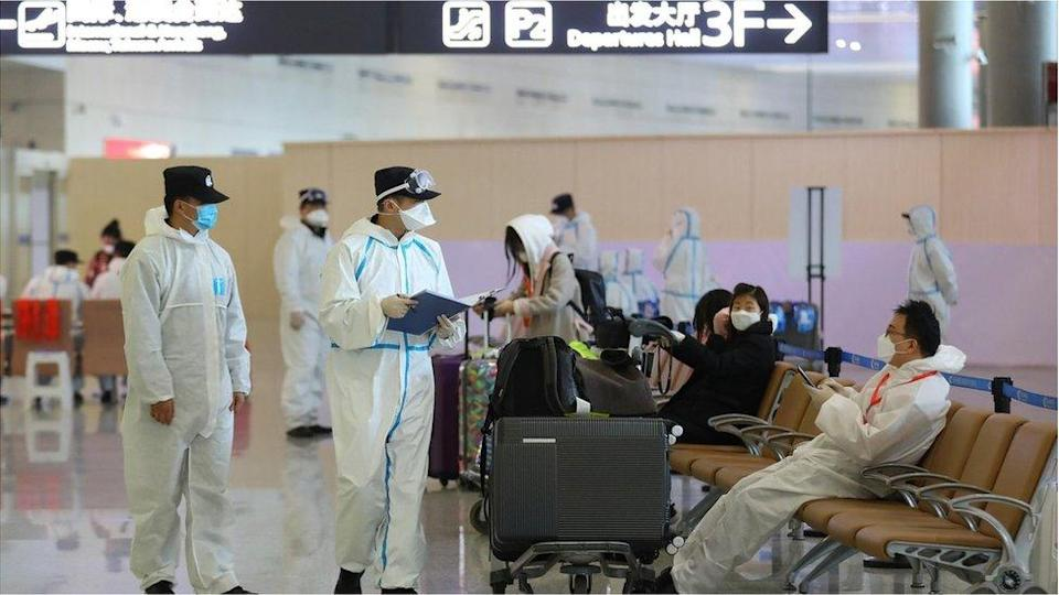 A staff member wearing a protective suit talks with an inbound passenger at Nanjing Lukou International Airport amid the coronavirus outbreak on March 16, 2020 in Nanjing, Jiangsu Province of China.