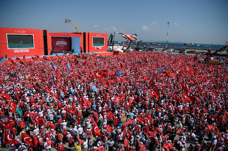 Demonstrators wave Turkish national flags in front of giant screens in Istanbul on August 7, 2016 during a rally against failed military coup on July 15