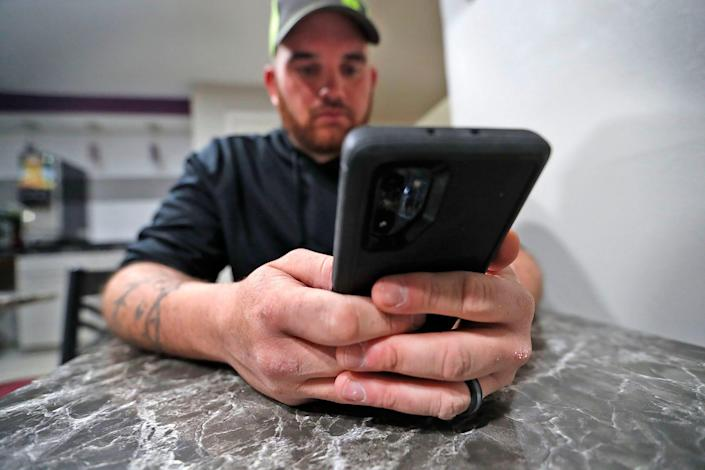 Austin Spain looks at his Facebook Messenger inbox on his phone Wednesday, Feb. 10, 2021. He has two decoy pages that he uses in his search for sexual predators online.