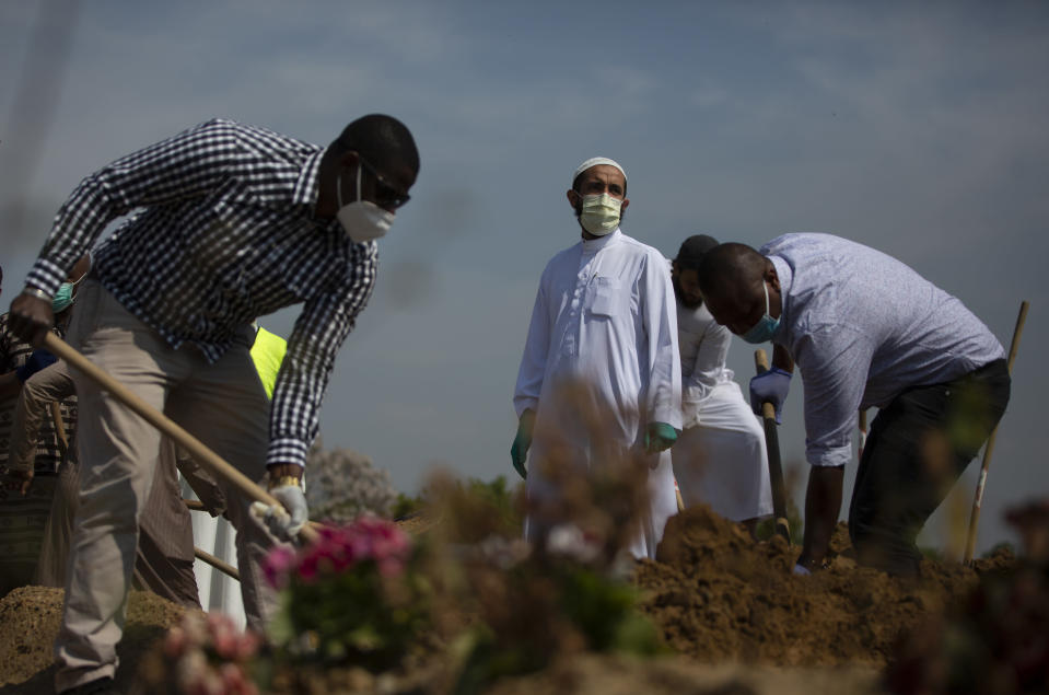 Mourners shovel dirt onto the grave of a Guinean man, who died of COVID-19 and who the family did not wish to identify by name, during a funeral at the cemetery of Evere, Belgium, Friday, April 24, 2020. Shops and restaurants in Belgium remain closed and weddings and funerals are limited in number during a partial lockdown to prevent the spread of the coronavirus. (AP Photo/Virginia Mayo)